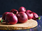 Red onions on wood board