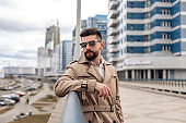 Portrait of bearded handsome man in beige jacket outdoors. Business concept with copy space on the urban street. Caucasian guy with black sunglasses on industrial background