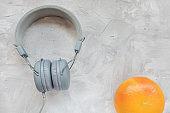 Grapefruit and headphones on gray