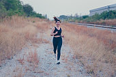 Athlete Thai woman running at the country road. Asian female runner endurance training in summer. Heathy lifestyle and sport recreation