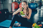 Beautiful young lady with salad in the Gym. Sport women exercise with healthy food. Mental health and wellness.