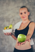 Beautiful young lady with apple and salad in the Gym. Sport women exercise with healthy food. Mental health and wellness.