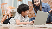Asian mother work home together with son. Mom teaching kid for online learning education. New normal lifestyle and family activity.