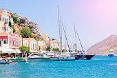 Wonderful view on colorful houses on rocks and sailing boats on dock of deep blue Mediterranian sea on Greek island Symi on sunbeams, holidays on exotic islands