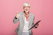 Happy senior businesswoman holding a document and showing OK sign
