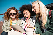 Three girlfriends using tablet and having fun outdoors