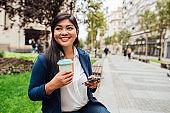 Beautiful Asian on a coffee break using smartphone