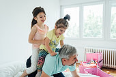 Two girls sitting on their grandpa's back and having fun