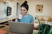 Young woman surfing the net and drinking coffee at home