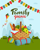 Family picnic concept. Wicker picnic basket full of healthy food, picnic blanket, kite, ball on grass