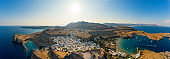 Breathtaking panoramic aerial view of Lindos town from the Acropolis of Lindos in Rhodes, Greece. Amazing colorful sunset scenery in Rhodes. Idyllic background above the Aegean sea. Dodecanese, Greece
