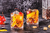 Old fashioned cocktail with cherries and orange twist