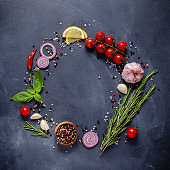 Herbs and condiments on black stone background