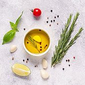 Herbs and condiments on light stone background.