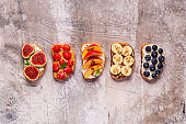 Homemade summer toast with cream cheese, nut butter and fruits and berries