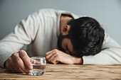sad man hand glass of vodka on desk