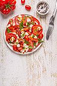 Italian caprese salad with sliced tomatoes, mozzarella cheese, basil, olive oil, balsamic vinegar