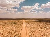 Drone aerial of camper van driving on rural desert dirt road through the iconic australian outback