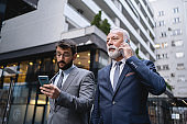 Businessmen using cellphones on the way to work