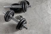 Steel dumbbells on the cement floor in the gym For bodybuilders