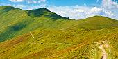 trail uphill through mountain range.