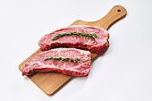 Fresh raw striploin steak on wooden board on white background with rosmary top view