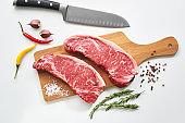 Two fresh raw striploin steak on wooden board