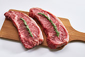 Two fresh raw striploin steak on wooden board on white background with rosmary side view