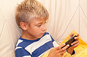 Little kid playing game or watching something on mobile smart phone