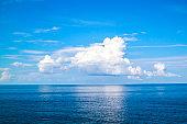 beautiful white clouds on blue sky over calm sea