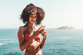 A phoning afro girl on the beach