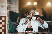 Black girl drinking coffee in a cafe