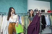 Two women in fashion boutique choose dress. Season holiday discounts for shopping