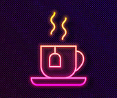 Glowing neon line Cup of tea with tea bag icon isolated on black background. Vector