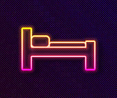 Glowing neon line Bed icon isolated on black background. Vector Illustration