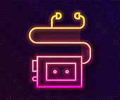 Glowing neon line Museum audio guide icon isolated on black background. Headphones for excursions. Vector