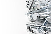 Lots of metal bolts and nuts. Tool for fixing. White background. Copy space