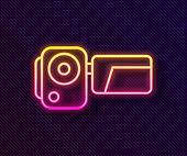 Glowing neon line Cinema camera icon isolated on black background. Video camera. Movie sign. Film projector. Vector Illustration