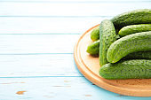 Fresh cucumbers on a wooden cutting board on blue wooden background