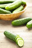 Fresh cucumbers in basket on grey background.