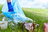 close-up blue gloved hand collecting plastic on green grass.