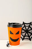 Paper cup with Halloween face in the blue background with spider. Vertical foto