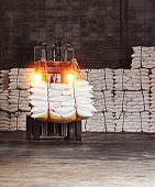 White sugar bags transferred to container for exporting. Forklift handling white sugar bag from warehouse for stuffing into container for export, vintage color.