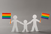 Happy same-sex family with LGBT flags on gray
