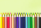 Set of colorful pencils on bright green background.