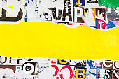 Torn yellow paper poster stripe on colorful collage from clippings with letters and numbers texture background. Copy space for text message.