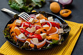 Hot salad with grilled bell pepper, Feta cheese, apricot and red onion. Close up. .Selective focus.