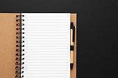 Recycled paper notebook opened on an empty sheet on black background. Copy space, top view.