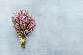 Bouquet of Pink Common Heather flowers on blue background. Copy space for text, top view. Flat lay