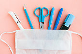 School supplies and medical mask on pastel pink background. Back to school concept. School quarantine concept